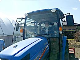 トラクター運転台に乗る中村